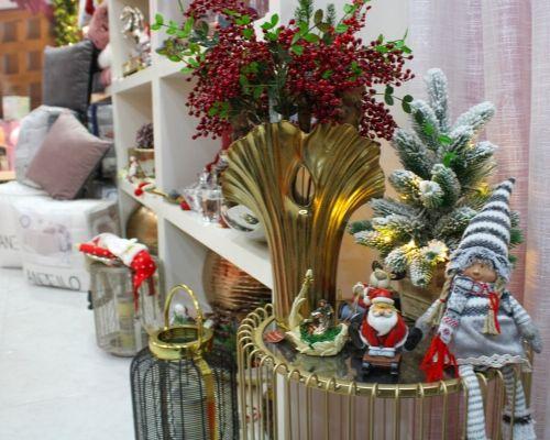 Azevinho e ramos de natal numa mesa com pai natal e presépio