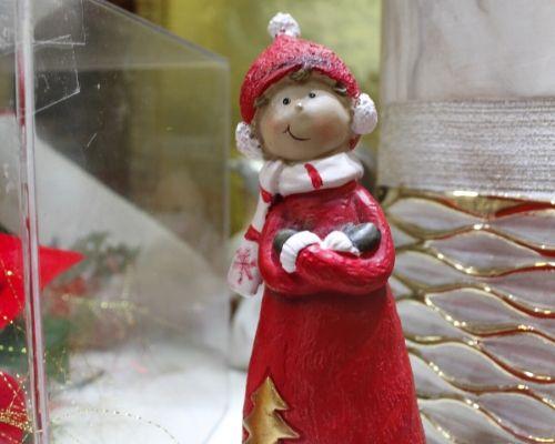 Bibelô de uma menina agasalhada para o frio com roupa de natal